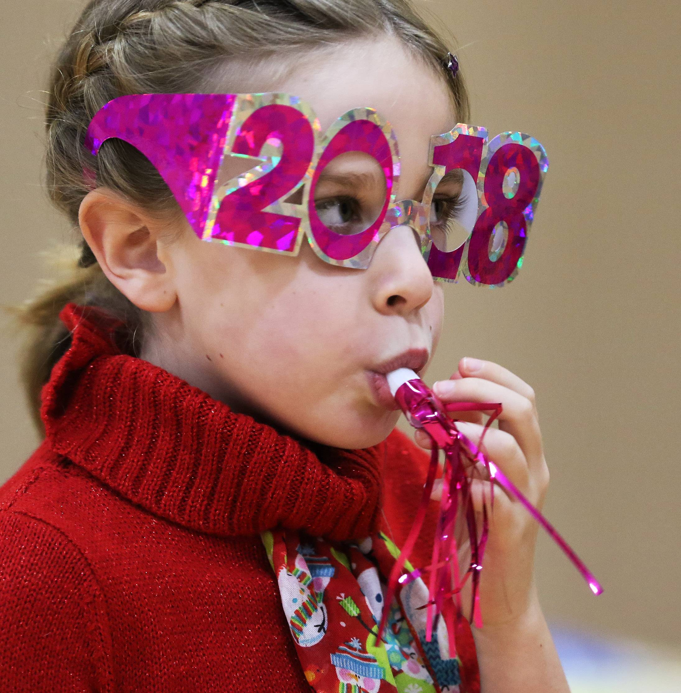 Seven-year-old Jodee Evans of Lake Zurich wears 2108 glasses as she blows a horn during Happy Noon Year at Wheeling Park District Community Recreation Center on Sunday. Families enjoyed dancing, games, a ballon drop, and a grape juice toast to welcome in the new year.