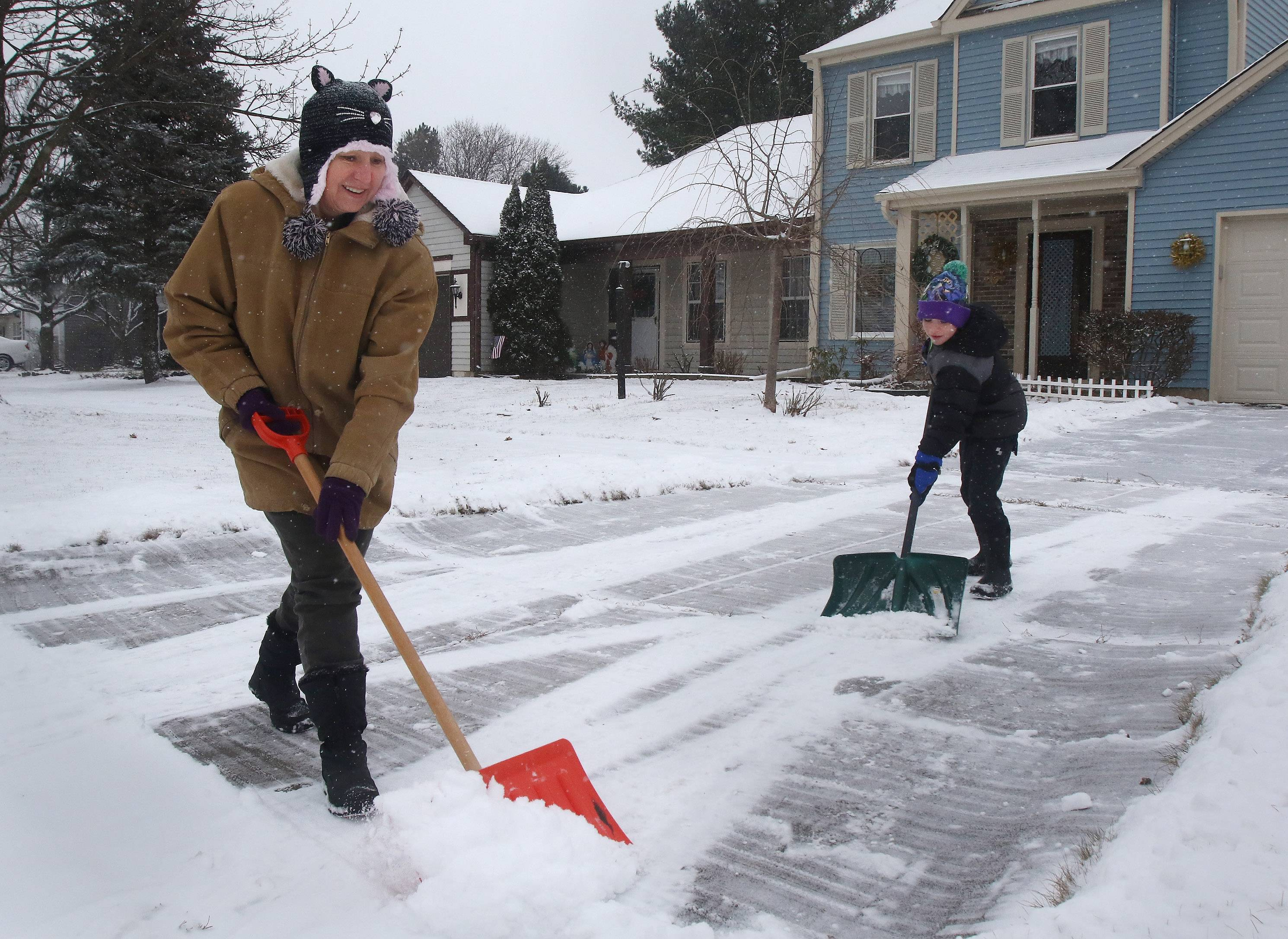 Mundelein resident Linda Wilson shovels her driveway with help from her neighbor Mason Freed, 7, as snow dropped around Lake County on Sunday.