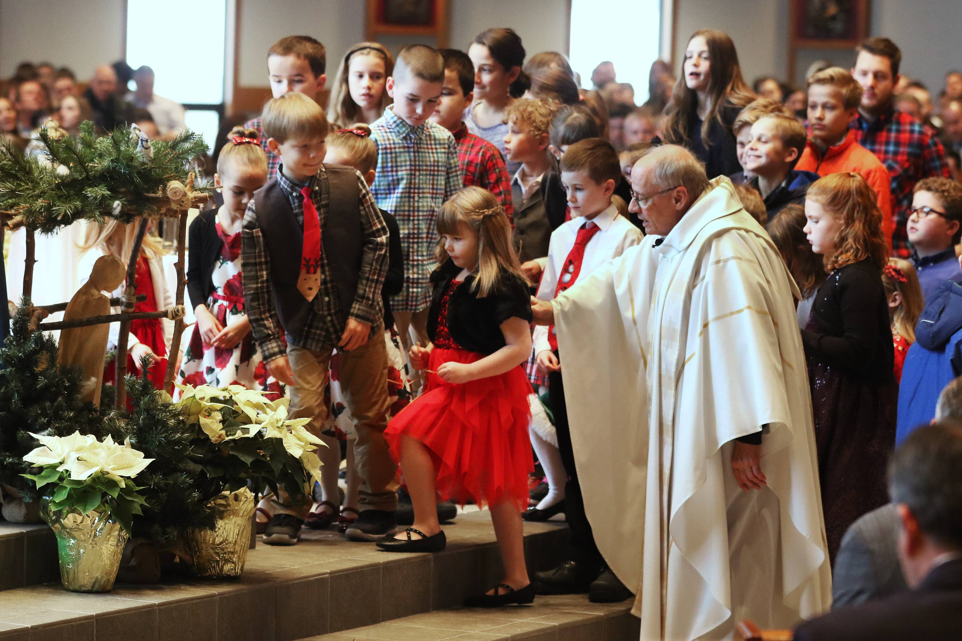 Father Joe Curtis directs children to come up to the Nativity scene and place straw around the baby Jesus before Christmas mass Sunday at St. Mary of Vernon Catholic Church in Indian Creek.