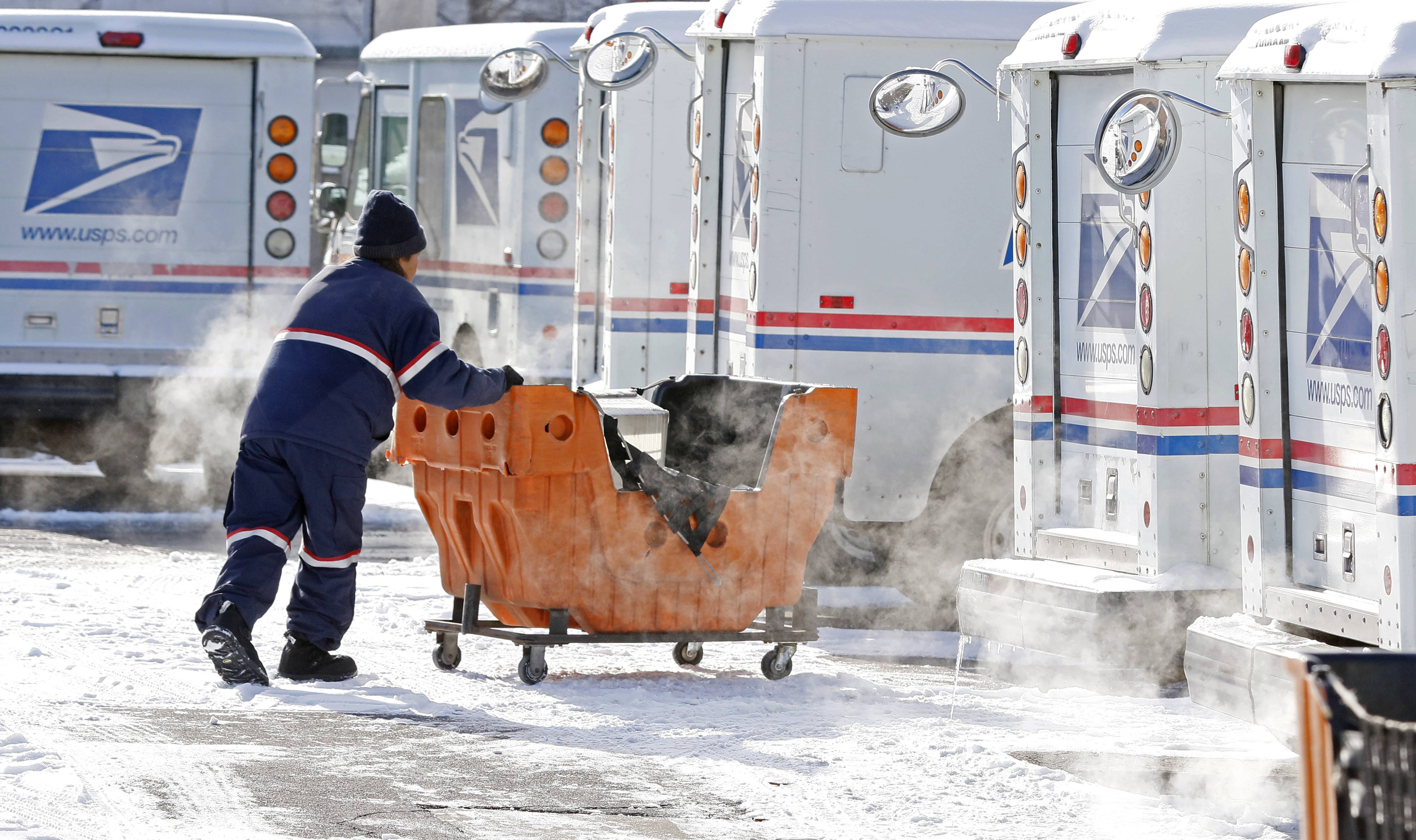 An Elmhurst Postal worker finishes loading his truck as frigid temperatures begin to blanket the area for the next week.