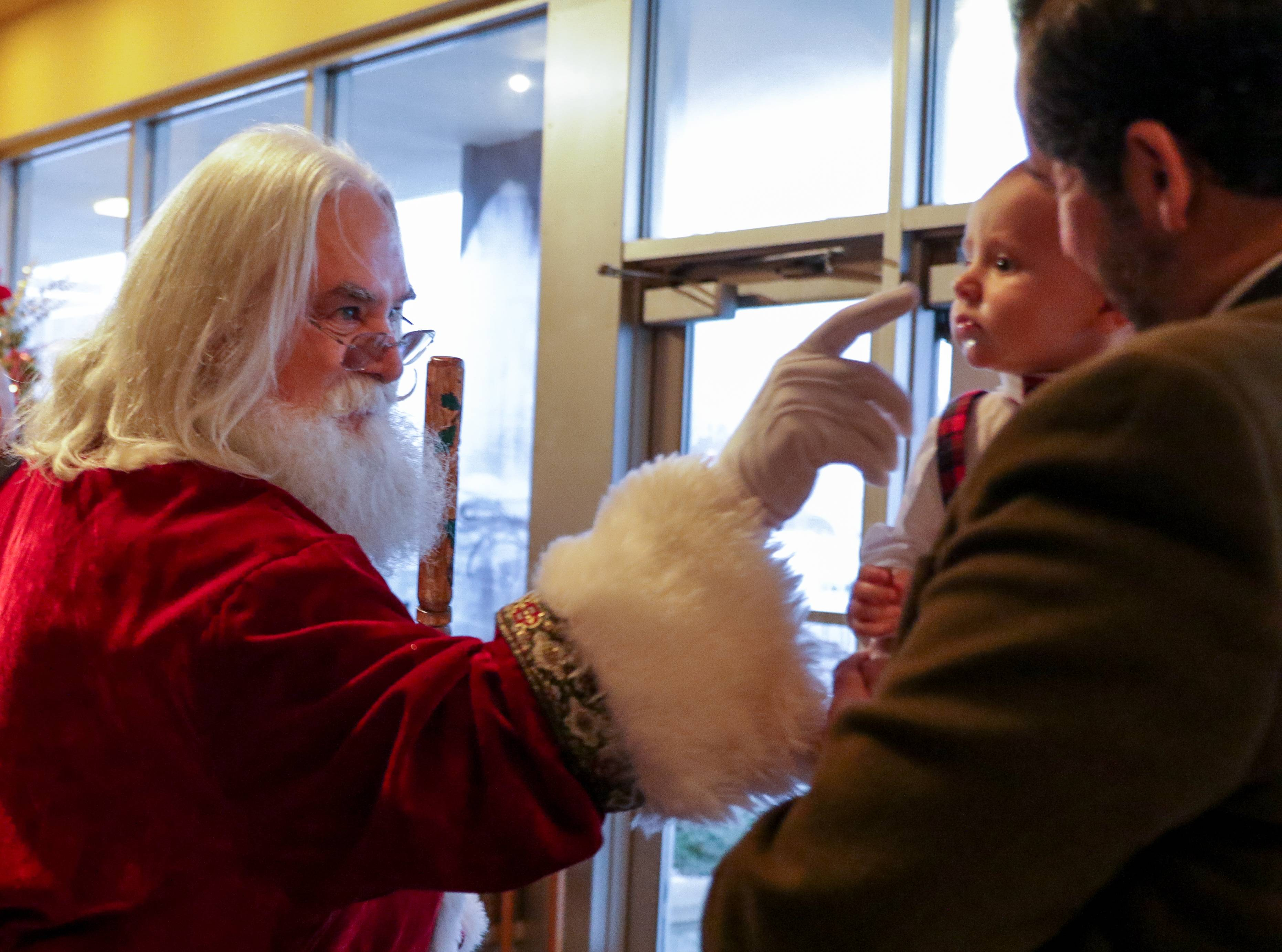 Santa greets Peter Messacar, with his son Colin, five months, after the Children's Christmas Mass at Immaculate Conception Church in Elmhurst on Sunday. Santa is played by Bob Hildreth, of Elgin and this is the fourth year of being part of children's service.