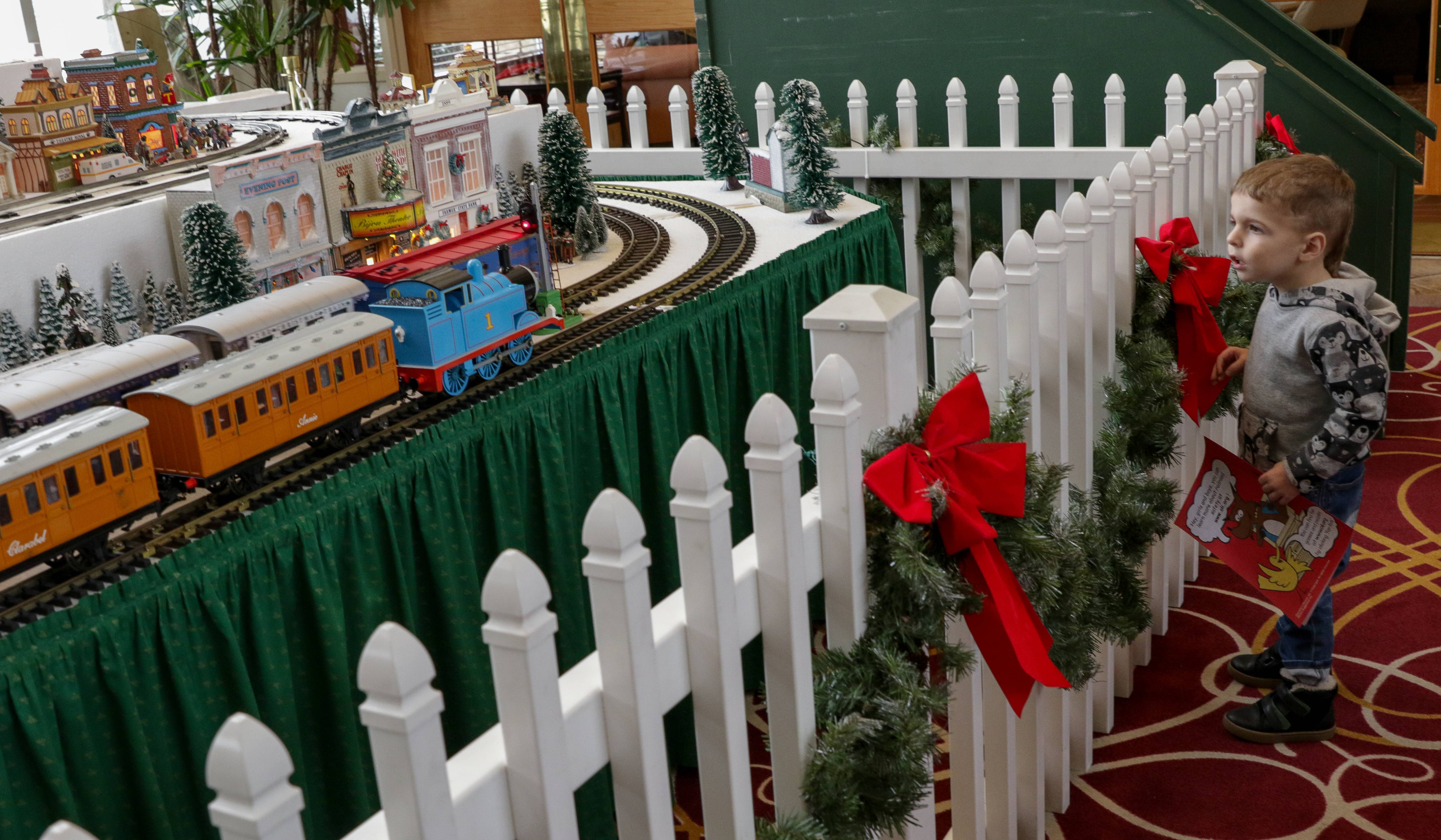 Elliott Bobbe, 2, checks out the holiday train display in the Prairie Lodge at Sun City in Huntley on Sunday. The train is set up by the Kishwaukee Valley and Eakin Creek Model Railroad Club of Sun City. Elliott lives in Kansas and was at Sun City to visiting his grandparents.