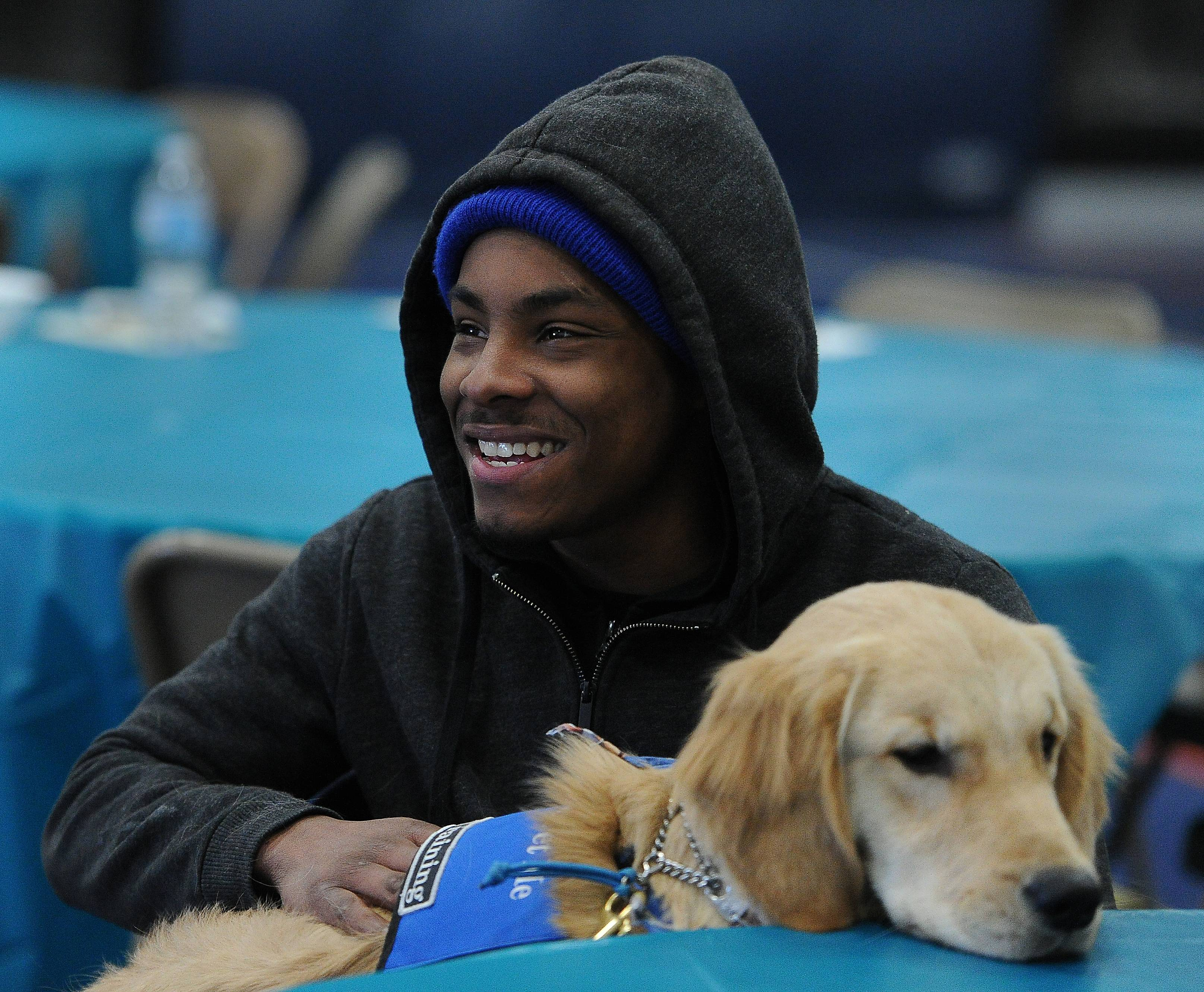 Darius Robinson, 19, of Carol Stream hangs out with Hope the Golden Retriever comfort dog at Our Savior Lutheran Church in Carol Stream. A Christmas party for about twenty homeless people was provided in which gift cards for food and gas along with a big meal treated both men and women.