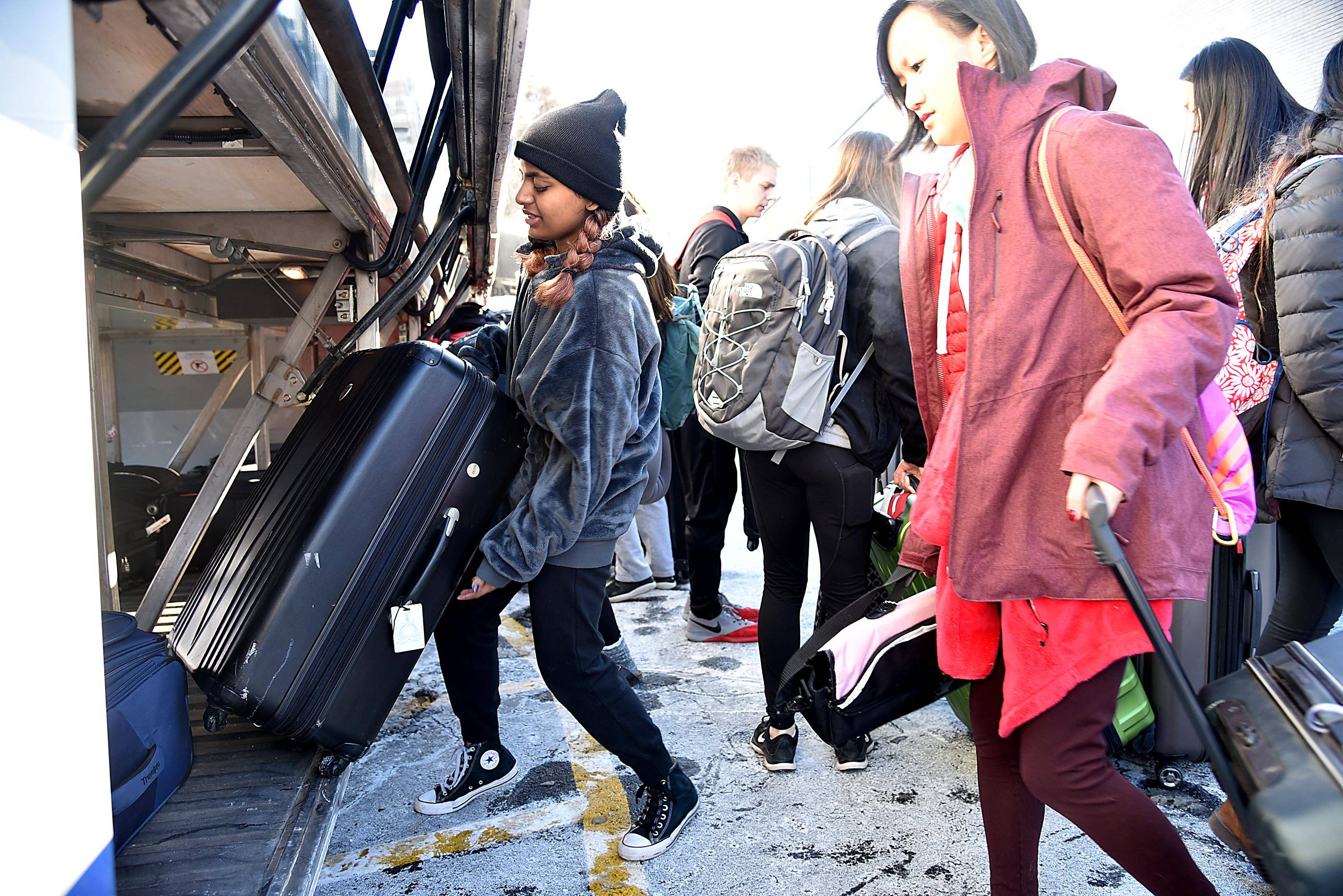 Barrington High School marching band members load baggage on buses to O'Hare International Airport for a flight to London Wednesday.