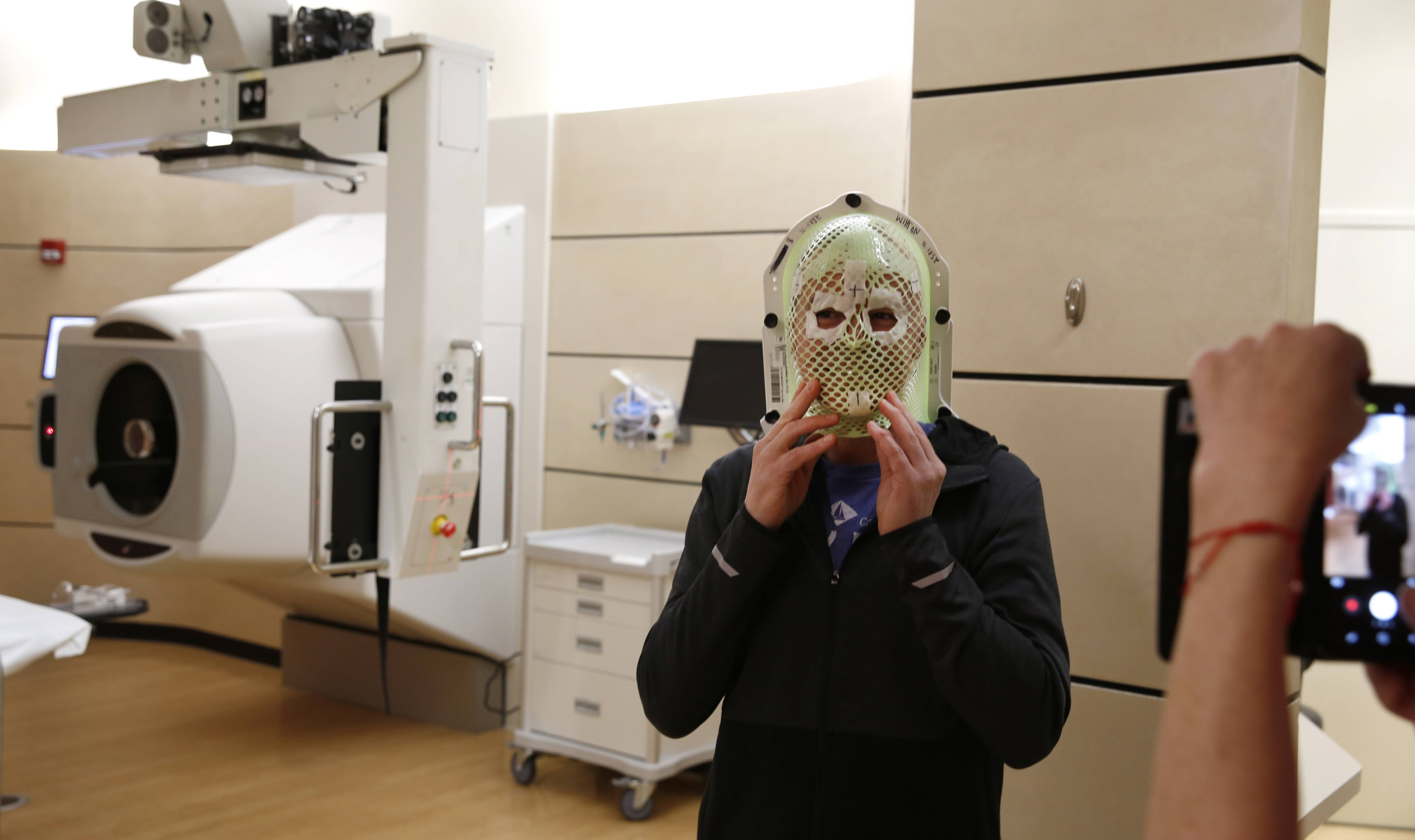 Dale Newman displays his face shield to take a photograph for his wife Amber in the treatment room at the Northwestern Medicine Proton Center in Warrenville, where he undergoes 8-week daily radiation treatments for a brain tumor.
