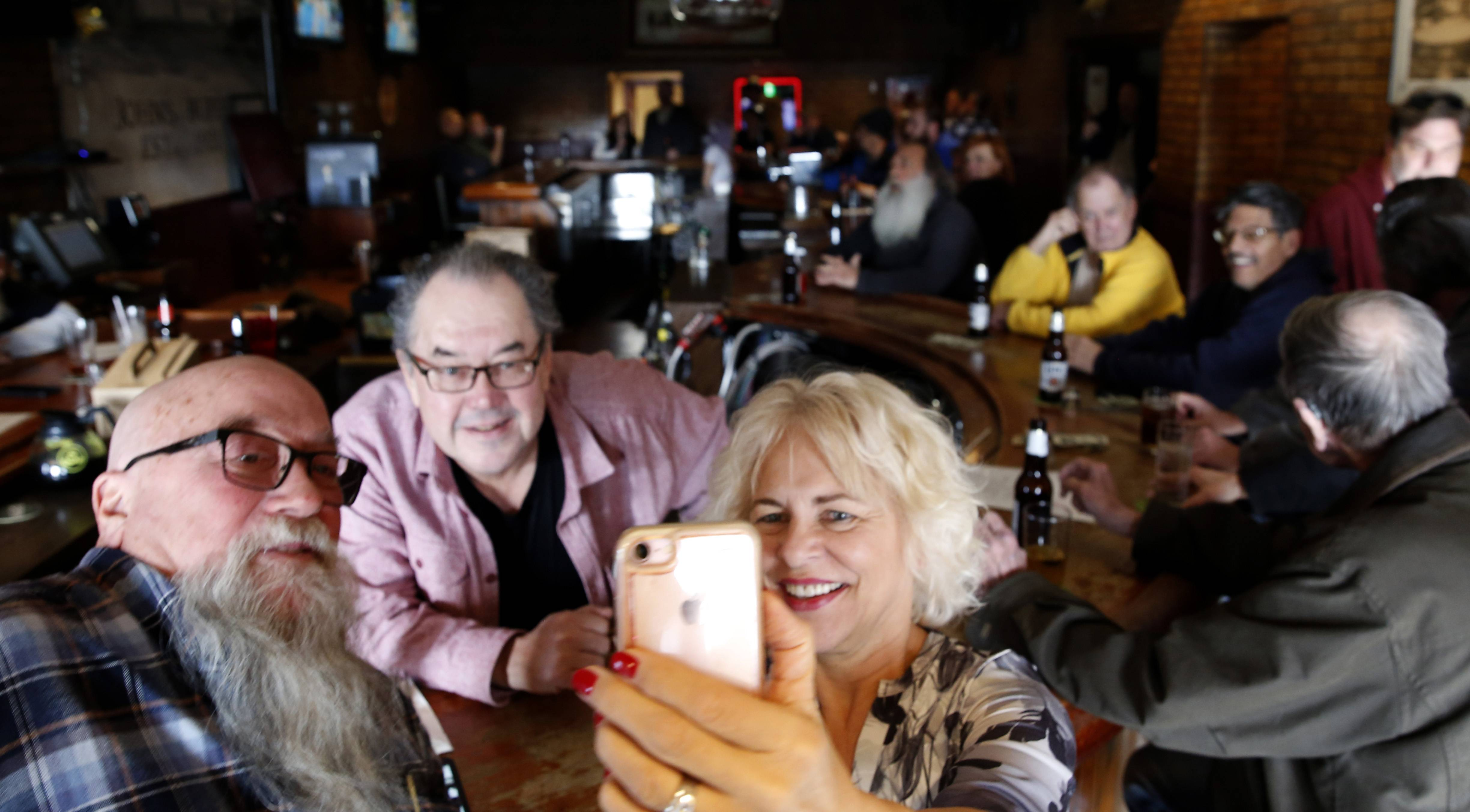 Mark and Sue Bosman, of Winfield take a selfie with John C. Karwoski, center, owner of John's Tavern in downtown Winfield. John's is closing its doors for the last time after being purchased by Northwestern Medicine. Mark Bosman said he had been coming to John's Tavern for 46 years.