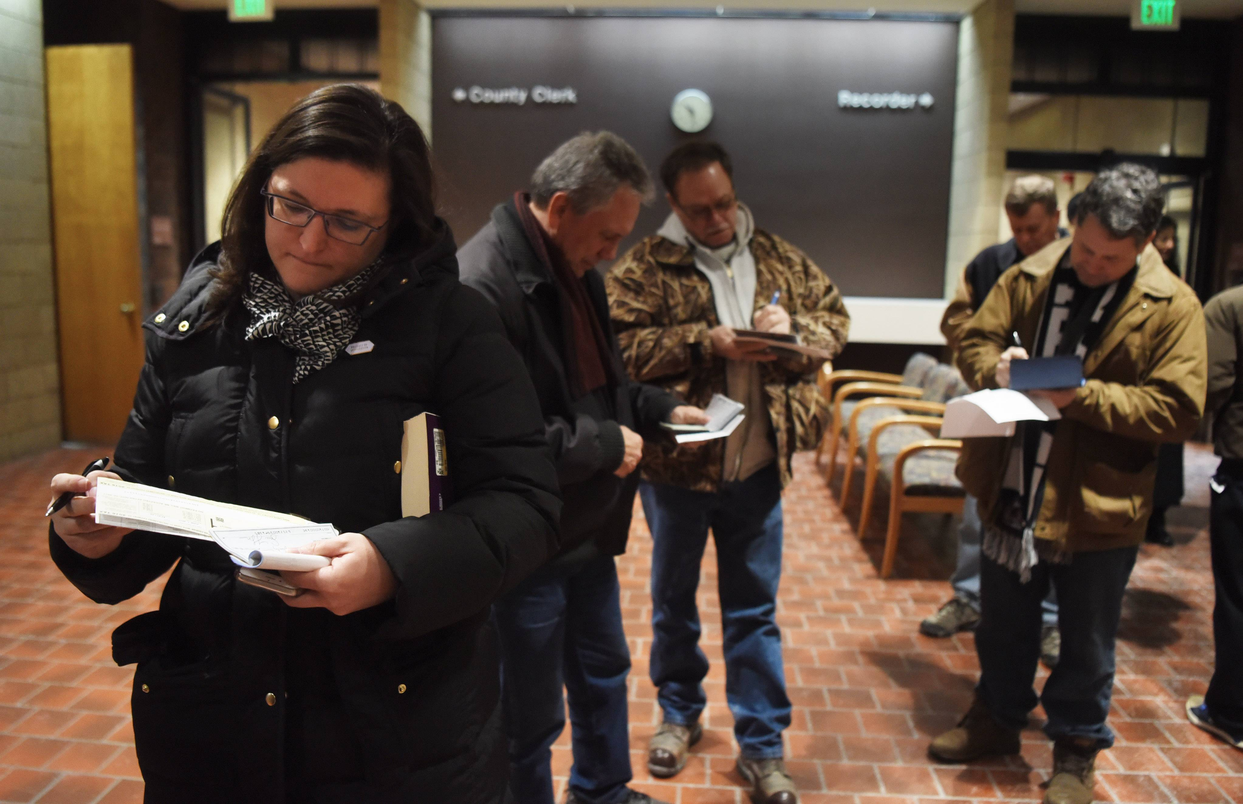Susan Wilson, of Elmhurst writes a check while standing in line to pay her property taxes at the DuPage County government building in Wheaton Friday.