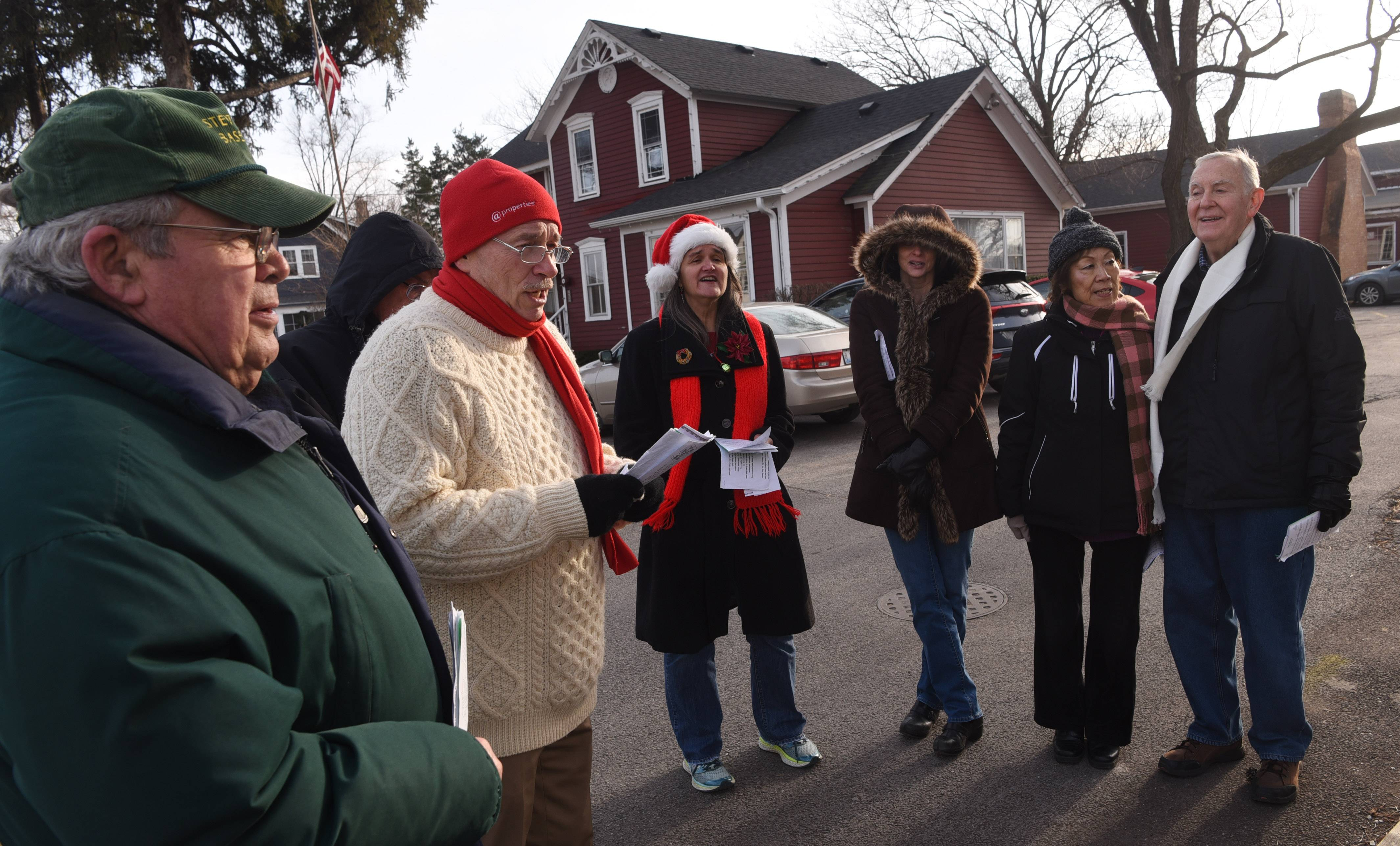 Kermit Lambert, left, of Buffalo Grove, and Tom Clark of Long Grove, second from left, are among a group singing Christmas carols in downtown Long Grove Saturday.