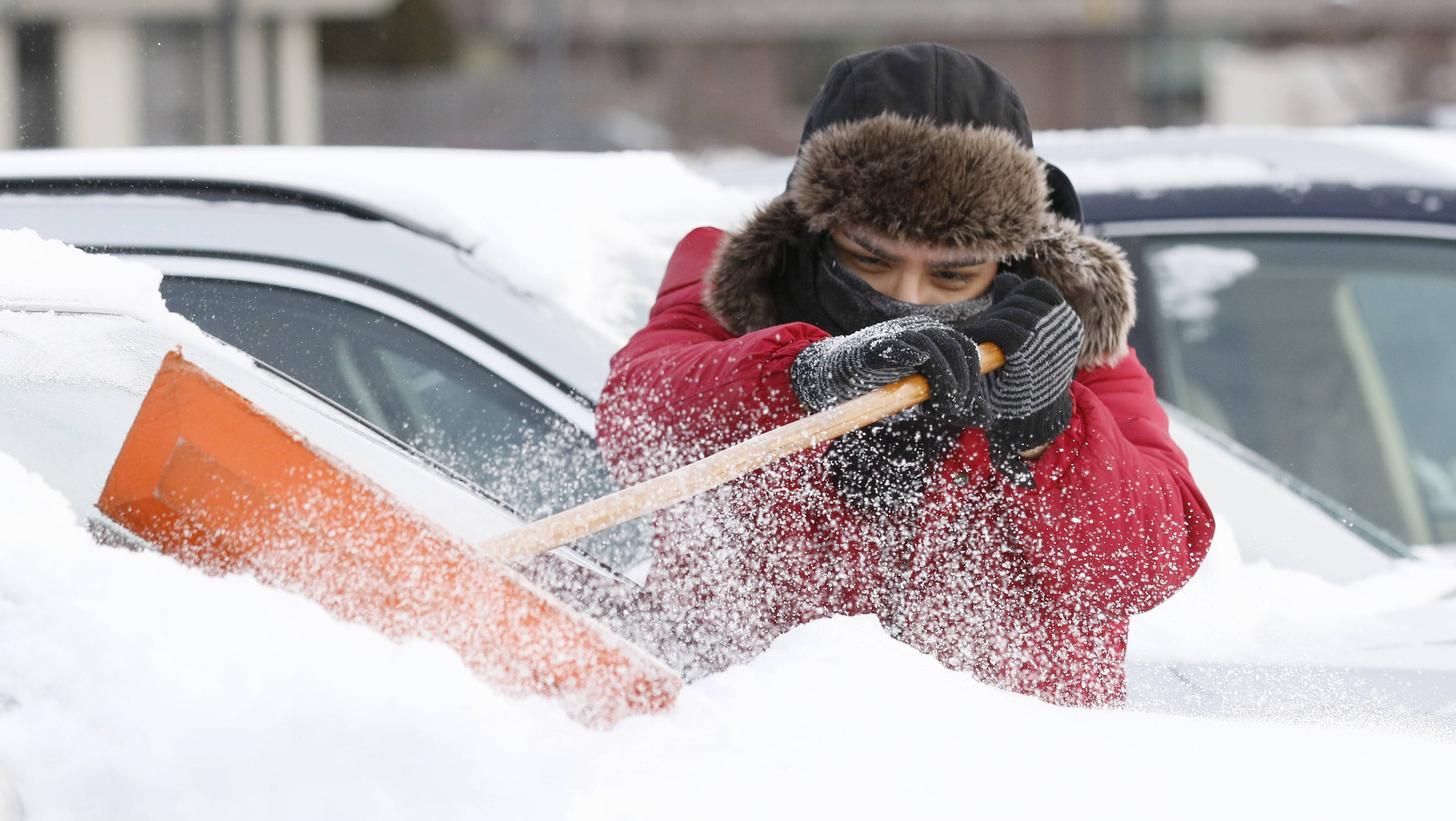 Eduardo Hernandez works to clear snow off cars at McGrath Lexus of Westmont.