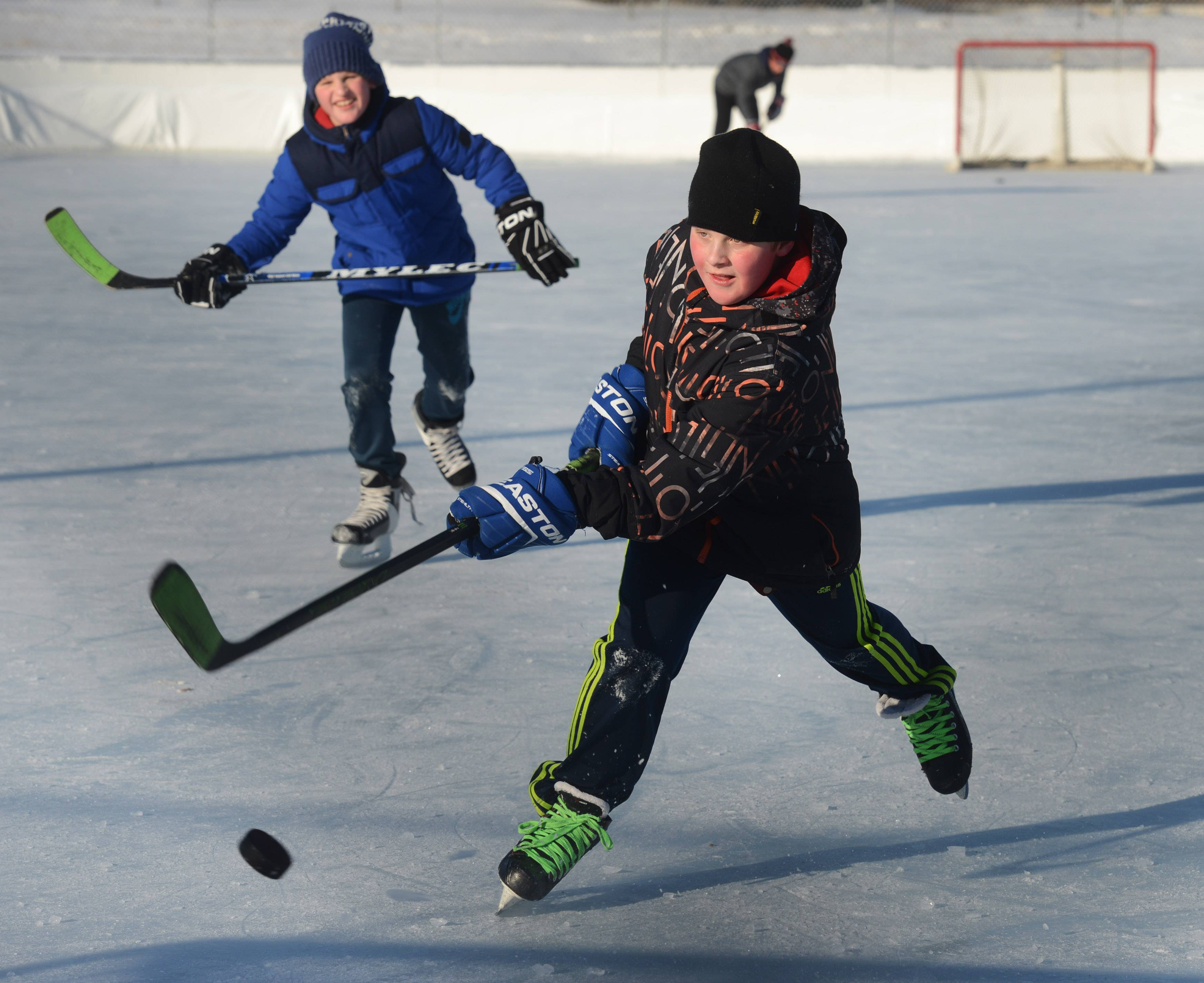 Alan Gielczynski, 10, of Grayslake shoots while playing hockey in seven-degree weather with his brother, Matthew, 12, on the outdoor rink at the Libertyville Sports Complex Tuesday.