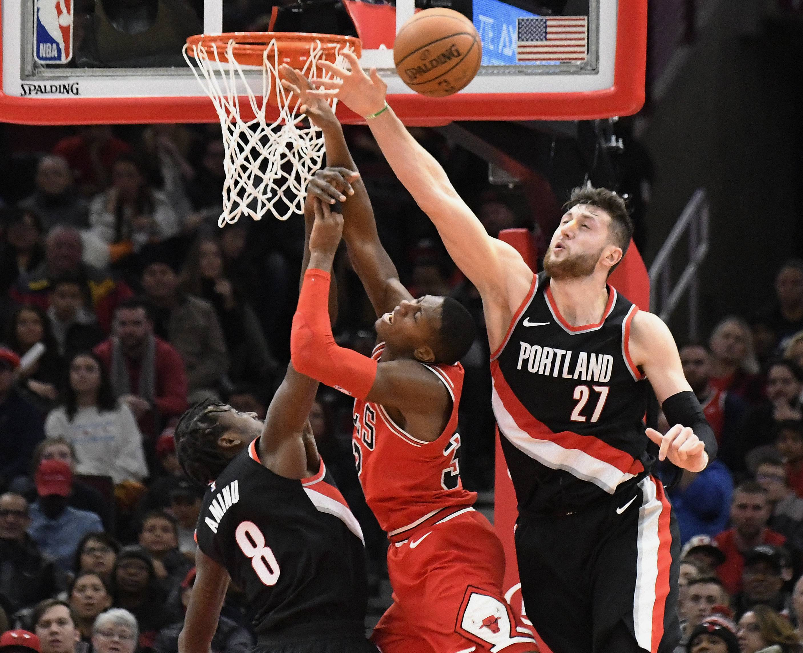 Portland Trail Blazers center Jusuf Nurkic (27) forward Al-Farouq Aminu (8) defend Chicago Bulls guard Kris Dunn, center, during the second half of an NBA basketball game, Monday, Jan. 1, 2018, in Chicago. The Trail Blazers won 124-120 in overtime. (AP Photo/David Banks)