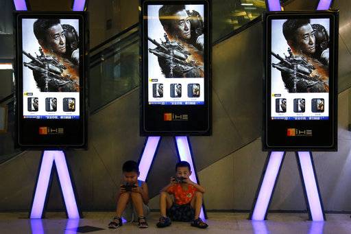"FILE - In this Aug. 10, 2017, file photo, children use smartphones near monitors displaying Chinese action movie ""Wolf Warrior 2"" at a cinema in Beijing. China's total domestic movie ticket sales rose 13.5 percent in 2017 to 55.9 billion yuan ($8.6 billion), a state news agency said Monday, Jan. 1, 2018. The top-grossing title was the mainland-made action picture ""Wolf Warrior 2,"" which took in 5.7 billion yuan ($875 million), the Xinhua News Agency said, citing data from the State Administration of Press, Publication, Radio, Film and Television."
