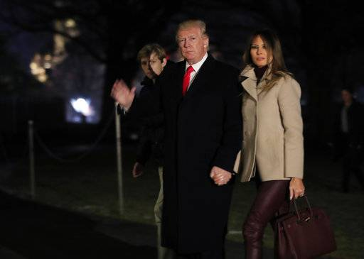 President Donald Trump together with first lady Melania Trump and their son Barron Trump waves as he returns to the White House in Washington, Monday, Jan. 1, 2018, from a holiday break at his Mar-a-Lago estate in Palm Beach, Fla. (AP Photo/Manuel Balce Ceneta)