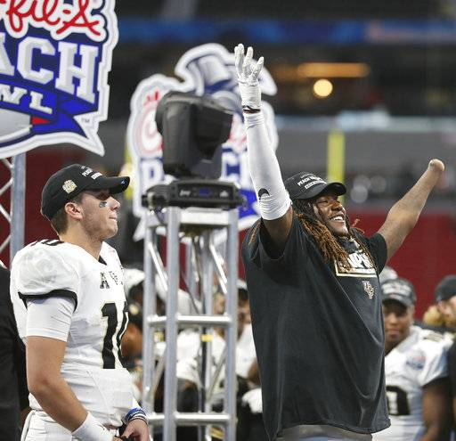 Central Florida linebacker Shaquem Griffin, right, and Central Florida quarterback McKenzie Milton (10) celebrate after the Peach Bowl NCAA college football game against Auburn, Monday, Jan. 1, 2018, in Atlanta. Central Florida won 34-27. (AP Photo/John Bazemore)