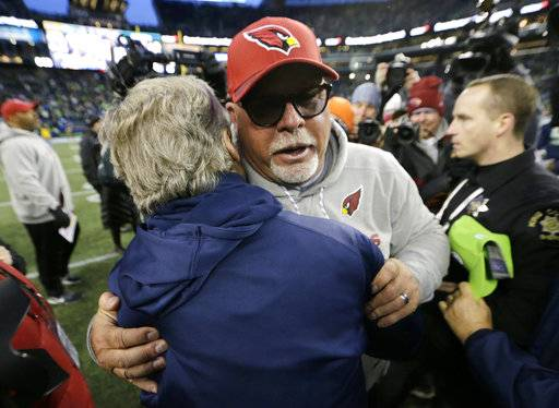 Arizona Cardinals head coach Bruce Arians, front right, hugs Seattle Seahawks head coach Pete Carroll, left, after an NFL football game, Sunday, Dec. 31, 2017, in Seattle. (AP Photo/John Froschauer)