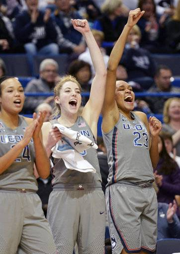Connecticut's Napheesa Collier (24), Katie Lou Samuelson (33), and Azura Stevens (23), UConn's starters, cheer for their teammates at the end of an NCAA college basketball game against Memphis, Sunday, Dec. 31, 2017, in Hartford, Conn. UConn won 97-49. (AP Photo/Stephen Dunn)