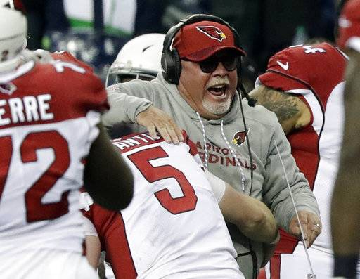 Arizona Cardinals head coach Bruce Arians is hugged by quarterback Drew Stanton (5) after Seattle Seahawks kicker Blair Walsh missed a field goal at the end of an NFL football game, Sunday, Dec. 31, 2017, in Seattle. (AP Photo/Elaine Thompson)