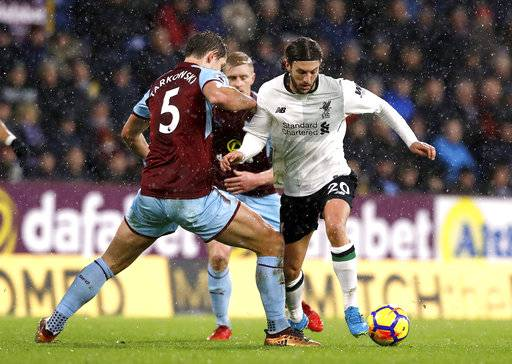 Burnley's James Tarkowski, left, and Liverpool's Adam Lallana battle for the ball during the English Premier League soccer match against Burnley at Turf Moor, Burnley, England, Monday Jan. 1, 2018. (Martin Rickett/PA via AP)