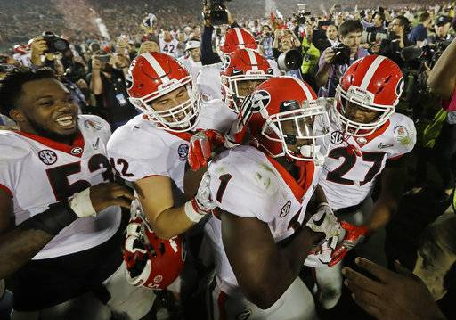 Georgia tailback Sony Michel (1) celebrates with teammates after scoring the game-winning touchdown in the second overtime period to give Georgia a 54-48 win over Oklahoma in the Rose Bowl NCAA college football game, Monday, Jan. 1, 2018, in Pasadena, Calif (AP Photo/Doug Benc)