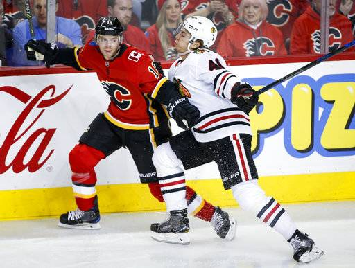 Chicago Blackhawks' John Hayden, right, checks Calgary Flames' Matt Stajan during the first period of an NHL hockey game Sunday, Dec. 31, 2017, in Calgary, Alberta. (Jeff McIntosh/The Canadian Press via AP)