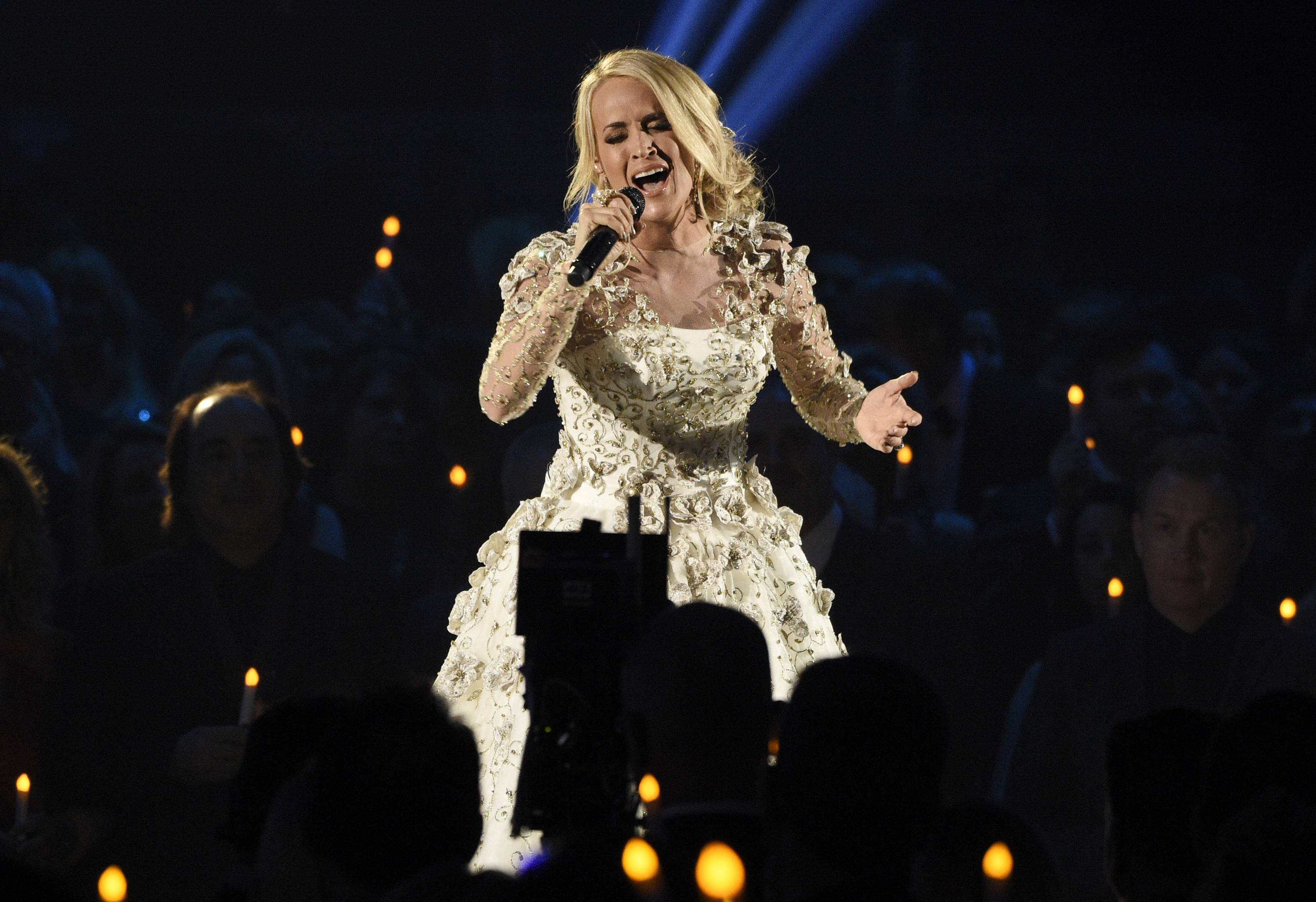 "FILE — In this Nov. 8, 2017, file photo, Carrie Underwood performs ""Softly and Tenderly"" during an In Memoriam tribute at the 51st annual CMA Awards at the Bridgestone Arena in Nashville, Tenn. Country singer Underwood is bringing in 2018 by sharing more details about more injuries that she suffered after a fall that broke her wrist. In a blog post to fans on New Year's Day, Underwood says she sustained a facial injury that required 40-50 stitches and that she's ""not quite looking the same."" (Photo by Chris Pizzello/Invision/AP, File)"