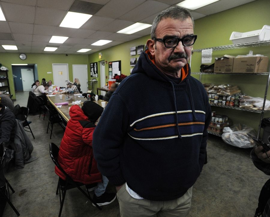 "Dennis Carollo of Arlington Heights says he attends the Hope Day Center on Tuesday at JOURNEYS The Road Home in Palatine because ""I'm homeless and I'm freezing."" Carollo said he spends most of his time reading his book."