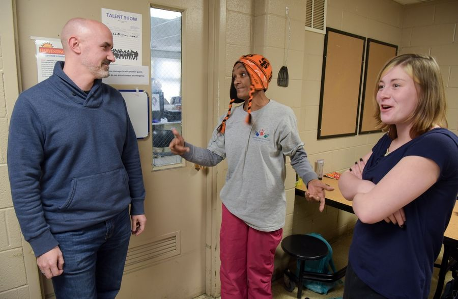 Hesed House Executive Director Ryan Dowd talks Tuesday with shelter guests Darlene Thomas and Mandalee Manning as the homeless services center stays open all day to give people refuge from the cold.