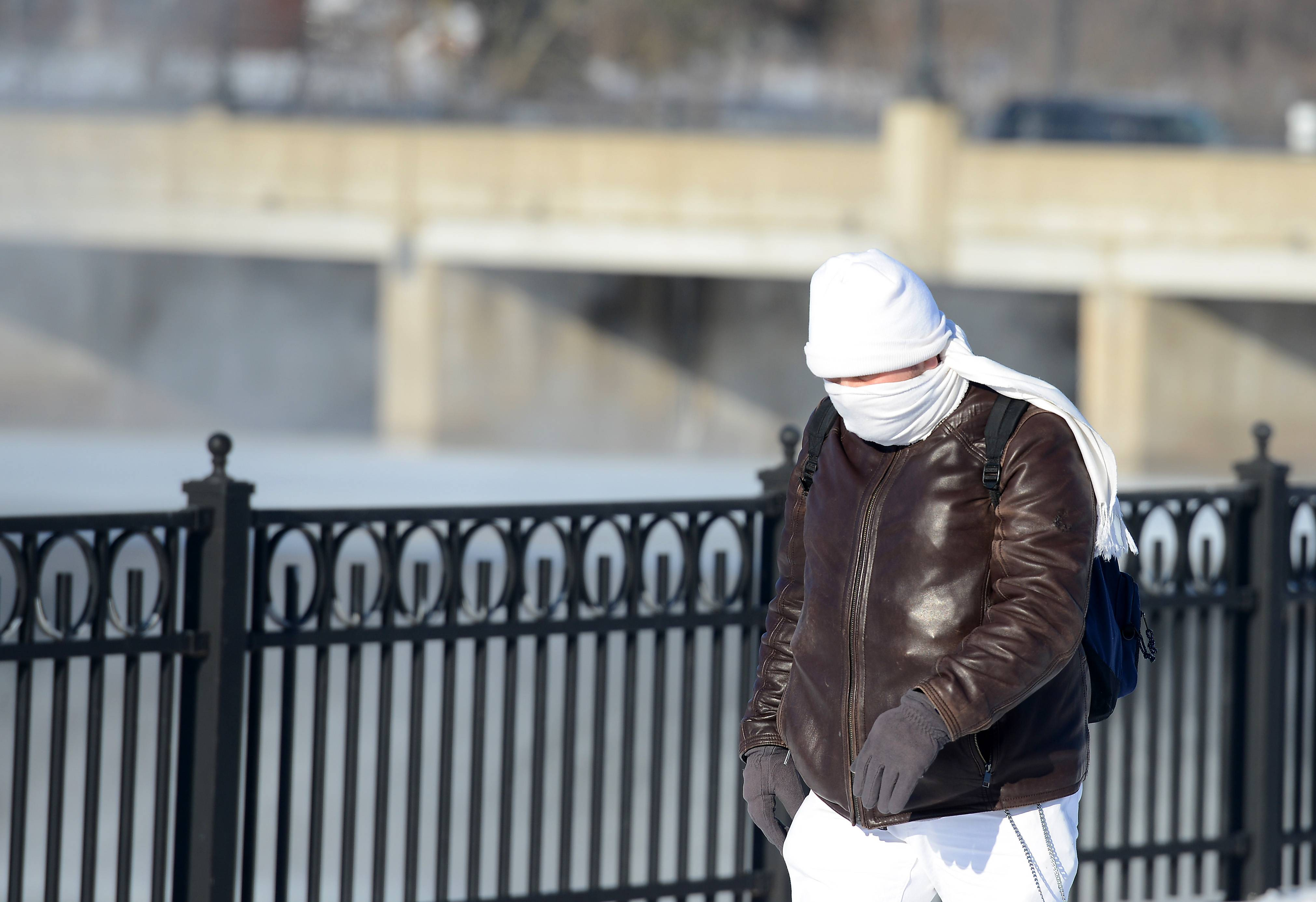 Isaac Frusti of Elgin tries to stay warm Tuesday as he walks to catch a bus in downtown Elgin. Morning low temperatures were below zero around the Fox Valley.