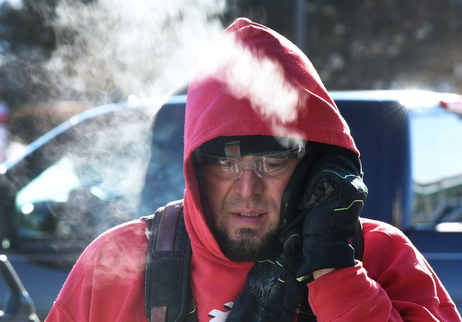 Steam rises from Bob Taylor's breath as the worker with Prodigy Construction in Crown Point, Indiana, takes a call from his boss in the cold Tuesday morning. Taylor was bundled up against the cold while working outside on a remodeling project at a Wauconda McDonald's restaurant.