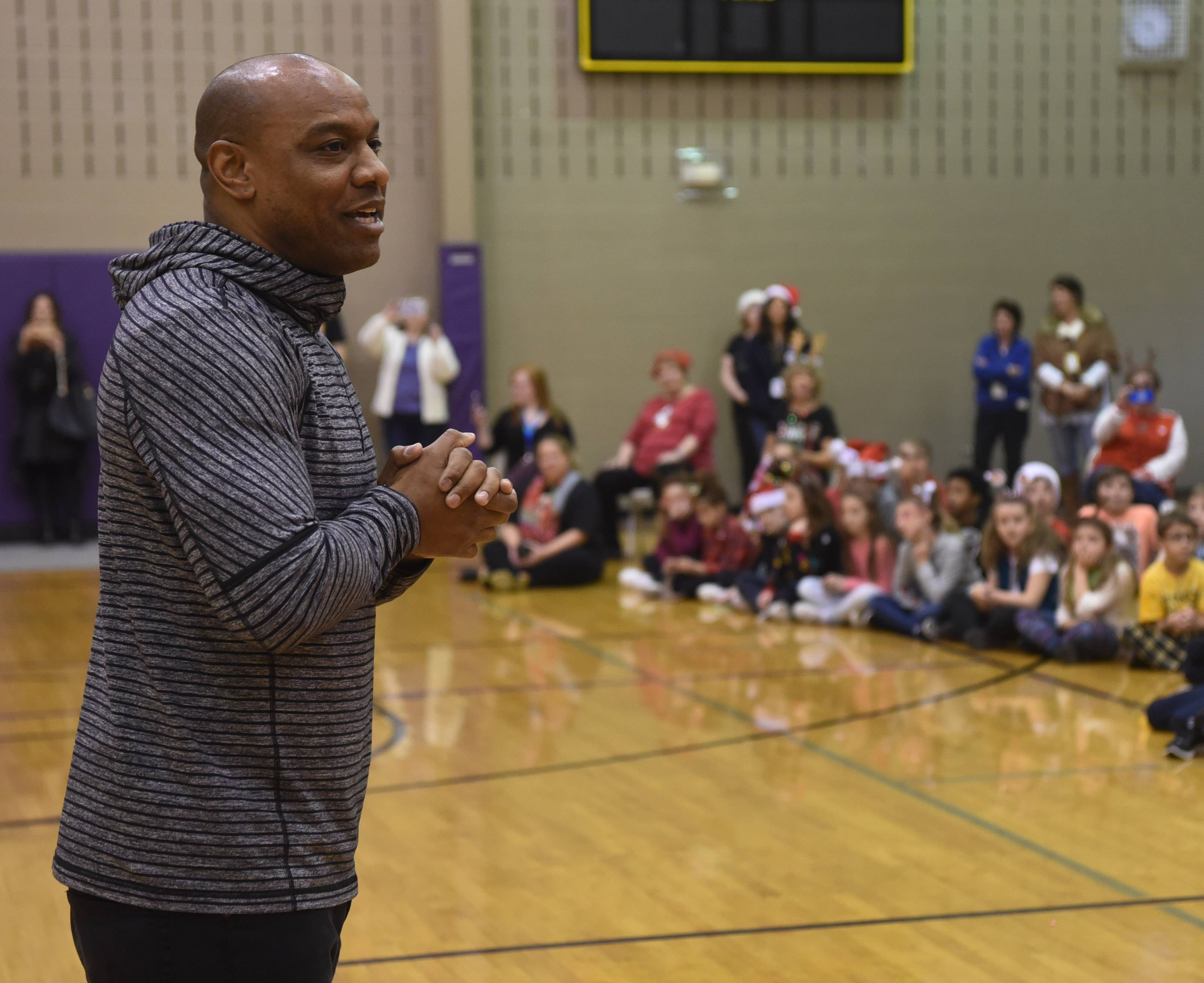 Jarrett Payton, son of Walter Payton, speaks during a celebration announcing that St. Hubert School in Hoffman Estates won first place in a diocese-wide food collection challenge.