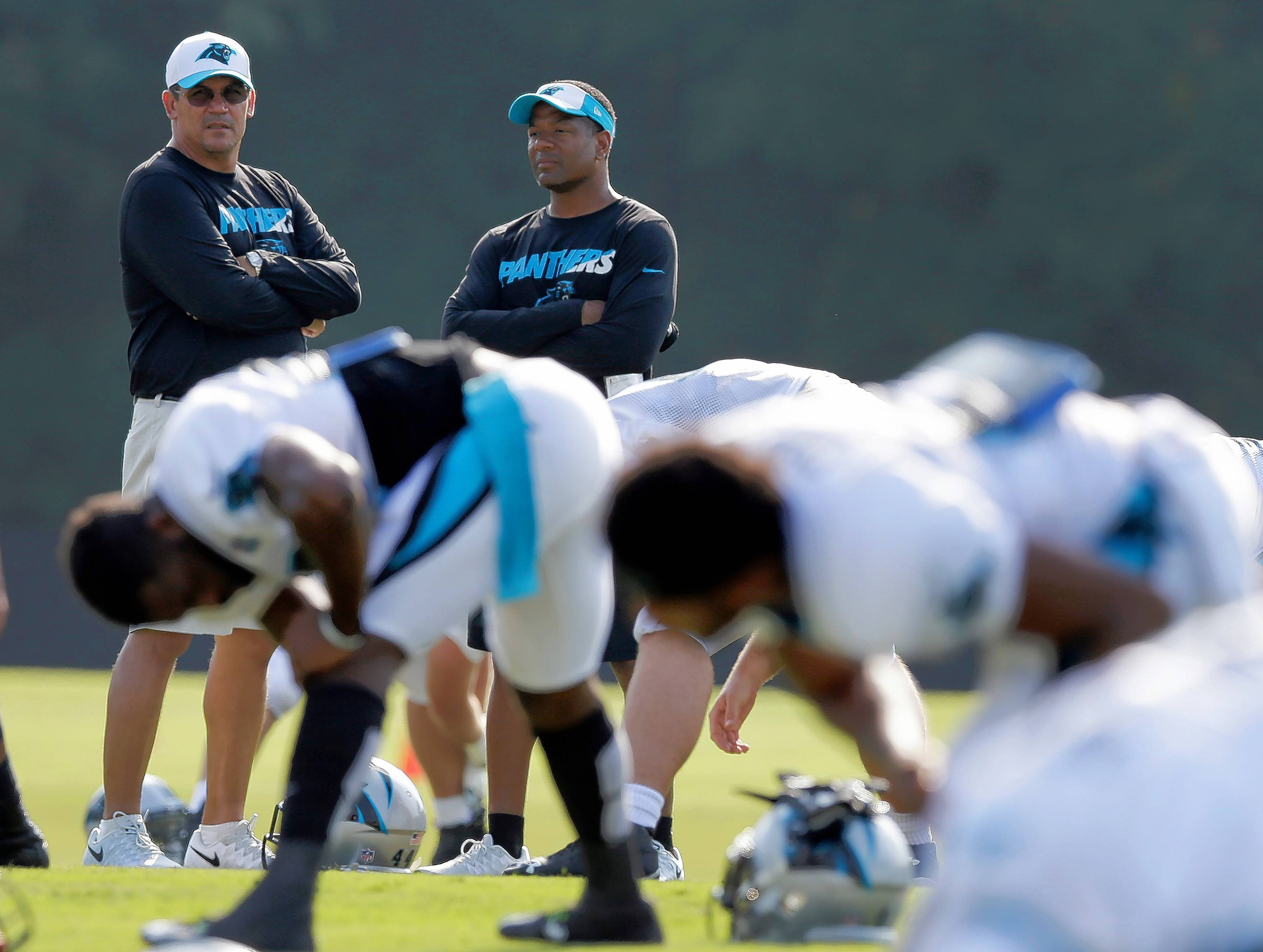 FILE -- In this Aug. 3, 2015, file photo, Carolina Panthers head coach Ron Rivera, left, talks with assistant head coach Steve Wilks, right, as players warm up during the NFL football team's training camp in Spartanburg, S.C. Rivera announced he has promoted Steve Wilks as the Panthers new defensive coordinator. Wilks has served as the Panthers defensive backs coach since 2012 and was given the additional title of assistant head coach by Rivera in 2015. He replaces Sean McDermott, who was hired as the Buffalo Bills head coach earlier this week.