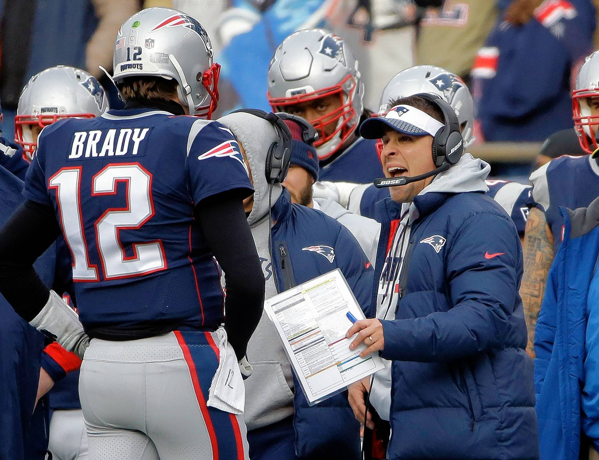 New England Patriots offensive coordinator Josh McDaniels, right, talks with quarterback Tom Brady (12) during a timeout in the first half of an NFL football game against the Buffalo Bills, Sunday, Dec. 24, 2017, in Foxborough, Mass.