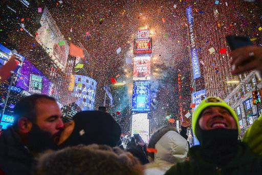 People celebrate New Year as confetti fall down after the countdown to midnight in Times Square during New Year's celebrations, Monday, Jan. 1, 2018, in New York. (AP Photo/Go Nakamura)