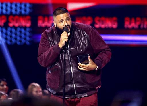 "FILE - In this Sunday, Nov. 19, 2017, file photo, DJ Khaled accepts the award for favorite song rap/hip-hop for ""I'm the One"" at the American Music Awards at the Microsoft Theater in Los Angeles. Weight Watchers International climbed after it struck a deal with producer and recording artist DJ Khaled, who will represent the brand to millions of follows on Snapchat, Twitter, Instagram and Facebook. (Photo by Matt Sayles/Invision/AP, File)"