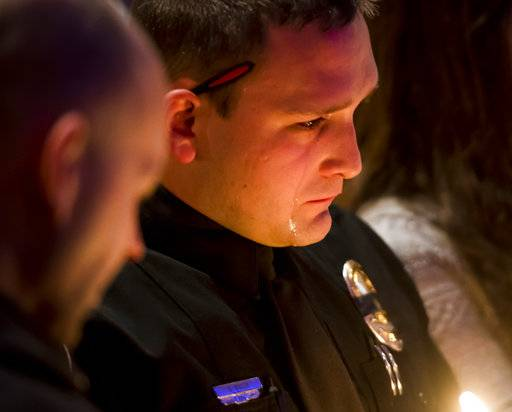 Officer Sean R. Bigler reacts during a candlelight vigil at Mission Hills Church on Monday, Jan. 1, 2018, for Deputy Zackari Parrish, 29, in Littleton, Colorado. A man who shot and killed the Colorado deputy and wounded several others along with a few civilians was an attorney and an Iraq war veteran who had posted videos online in recent months criticizing professors and law enforcement officials, authorities said Monday. (Dougal Brownlie/The Gazette via AP)