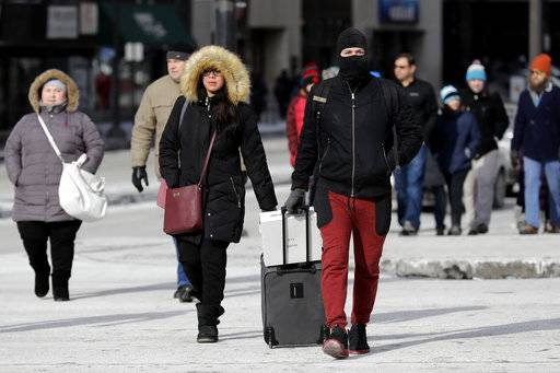 Pedestrians are bundled up against frigid temperatures, Sunday, Dec. 31, 2017, in Chicago.