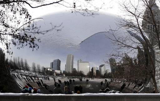 People visit a snow-covered Cloud Gate at Millennium Park in Chicago, Sunday, Dec. 31, 2017. Bitter cold temperatures are affecting parts of the U.S.