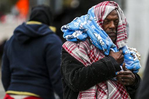 Michael Labingo wraps himself in blankets as the Star of Hope's Love in Action van delivers blankets and supplies to the homeless as temperatures hover in the 30s Tuesday, Jan. 2, 2018 in Houston. Plunging overnight temperatures in Texas brought rare snow flurries as far south as Austin, and accidents racked up on icy roads across the state. In the central Texas city of Abilene, the local police chief said more than three dozen vehicle crashes were reported in 24 hours.  (Michael Ciaglo/Houston Chronicle via AP)