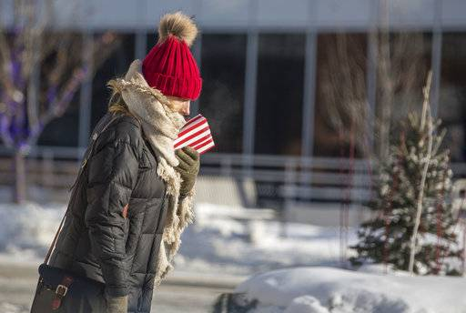 A woman is bundled up as she walks in subzero weather Tuesday, Jan. 2, 2018, in South Bend, Ind. The National Weather Service issued wind chill advisories and freeze warnings Tuesday covering a vast area from South Texas to Canada and from Montana through New England. (Santiago Flores/South Bend Tribune via AP)