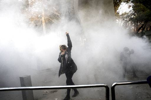 FILE - In this Saturday, Dec. 30, 2017 file photo taken by an individual not employed by the Associated Press and obtained by the AP outside Iran, a university student attends a protest inside Tehran University while a smoke grenade is thrown by anti-riot Iranian police, in Tehran, Iran. Iran has seen its largest anti-government protests since the disputed presidential election in 2009, with thousands taking to the streets in several cities in recent days. Travel restrictions and moves by the government to shut down social media networks have limited the ability of journalists to cover the ongoing unrest, which Iranian state television said has killed 12 people. (AP Photo, File) The Associated Press