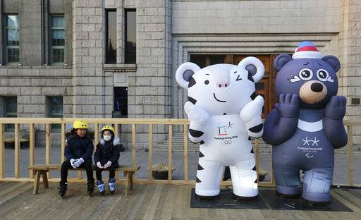 Children sit next to the 2018 Pyeongchang Winter Olympic Games' official mascots, a white tiger Soohorang, for the Olympics, and black bear Bandabi, right, for Paralympics, near Seoul Plaza Ice Rink in Seoul, South Korea, Tuesday, Jan. 2, 2018. South Korea on Tuesday offered high-level talks with rival North Korea to find ways to cooperate on next month's Winter Olympics in the South.