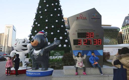 "Children pose in front of an electric board that shows the number of days left until the opening of 2018 Pyeongchang Winter Olympic Games as the official mascots, a white tiger ""Soohorang"" for the Olympic, left, and black bear ""Bandabi"" for the Paralympic, are displayed in Seoul, South Korea, Tuesday, Jan. 2, 2018. South Korea on Tuesday offered high-level talks with rival North Korea to find ways to cooperate on next month's Winter Olympics in the South."
