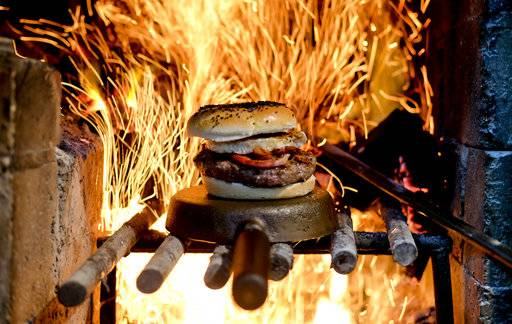 In this Nov. 11, 2017 photo, a hamburger sits for display before a wood-fueled fire at Kon Kon restaurant in Buenos Aires, Argentina. Argentine cuisine has long been known worldwide for its barbecued beef, but chefs there are now taking the country's passion for grilling with wood to a new level and earning international recognition by experimenting with new dishes in open-fire ovens, including fast food.