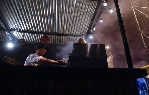 "In this Nov. 11, 2017 photo, smoke rises above a cook preparing plates of food using a wood-burning oven at Buenos Aires's food fair Masticar in Buenos Aires, Argentina. Food critic and journalist Nico Visne says Argentine cooking is going through a very important moment. ""It's based in our gaucho (cowboy), indigenous and immigrant cooking, and there's this return to the real flavors and the fire."""