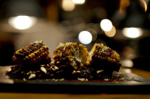 In this Nov. 17, 2017 photo, flame-cooked corn on the cob sits on a plate at Bestia restaurant in Buenos Aires, Argentina. Its co-owner, chef Nacho Trotta, traveled for weeks through Alabama, New Orleans and Texas to incorporate smoking and barbecue methods of southern cuisine.