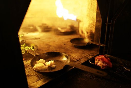 In this Nov. 13, 2017 photo, calamari cooks inside a wood-burning oven at Proper restaurant in Buenos Aires, Argentina. The restaurant, located in a refurbished auto-repair shop in Argentina's capital, was recently named in the Latin American edition of the prestigious San Pellegrino World's 50 Best Restaurants list.