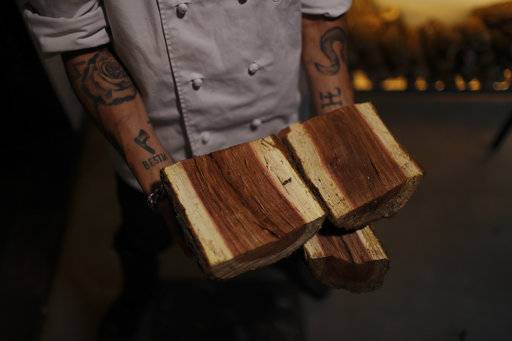 "In this Nov. 17, 2017 photo, chef Nacho Trotta shows the wood he uses to cook with at the restaurant he co-owns, Bestia, in Buenos Aires, Argentina. ""Firewood is the engine of this restaurant,"" he said. ""You can't get this type flavor from a gas grill or a frying pan."""