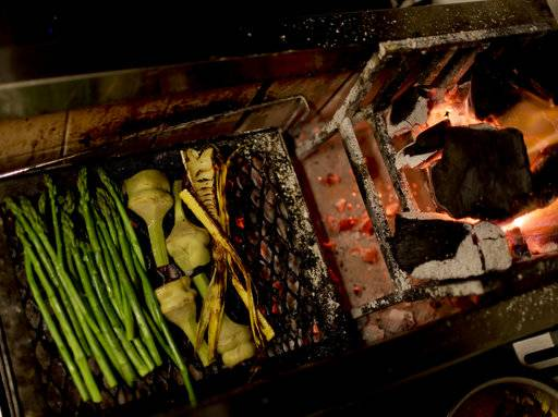 In this Nov. 9, 2017 photo, vegetables sit on a wood-burning grill at Grand Gran Dabbang restaurant in Buenos Aires, Argentina. While cooking by fire may be the oldest, most primitive way of cooking food, a growing number of chefs around the world have elevated wood-fire cooking to new heights at some of the most acclaimed restaurants.