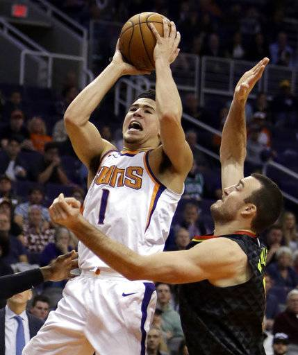 Phoenix Suns guard Devin Booker (1) drives on Atlanta Hawks guard Marco Belinelli during the second half of an NBA basketball game Tuesday, Jan. 2, 2018, in Phoenix. The Suns defeated the Hawks 104-103.