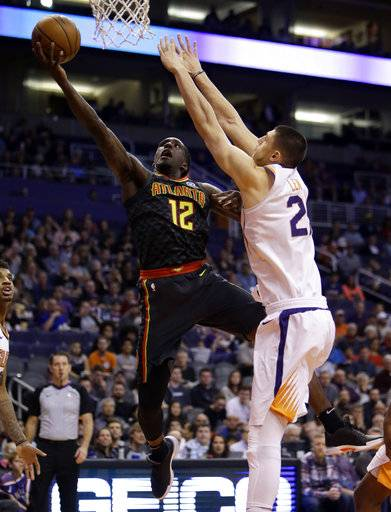 Atlanta Hawks forward Taurean Prince (12) drives past Phoenix Suns center Alex Len in the first half during an NBA basketball game, Tuesday, Jan. 2, 2018, in Phoenix.
